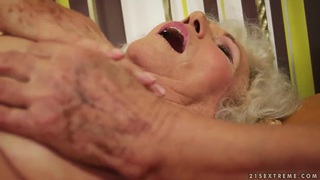 A very hairy granny stimulates her old clit